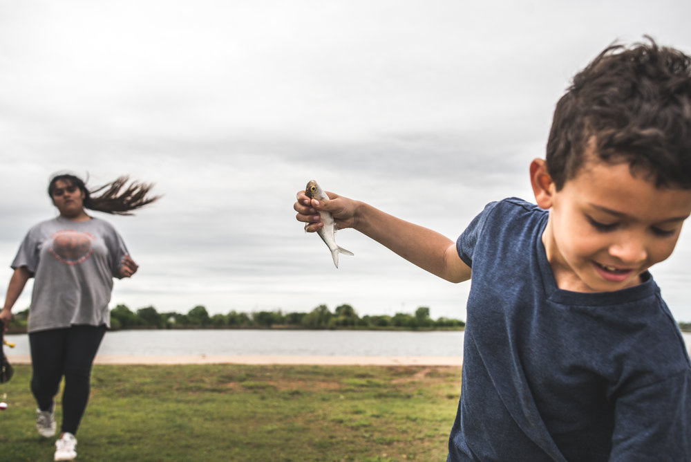 Color photo of a little boy in a blue shirt holding up a small fish while a girl in the background walks toward him to check it out, her pony tail swinging