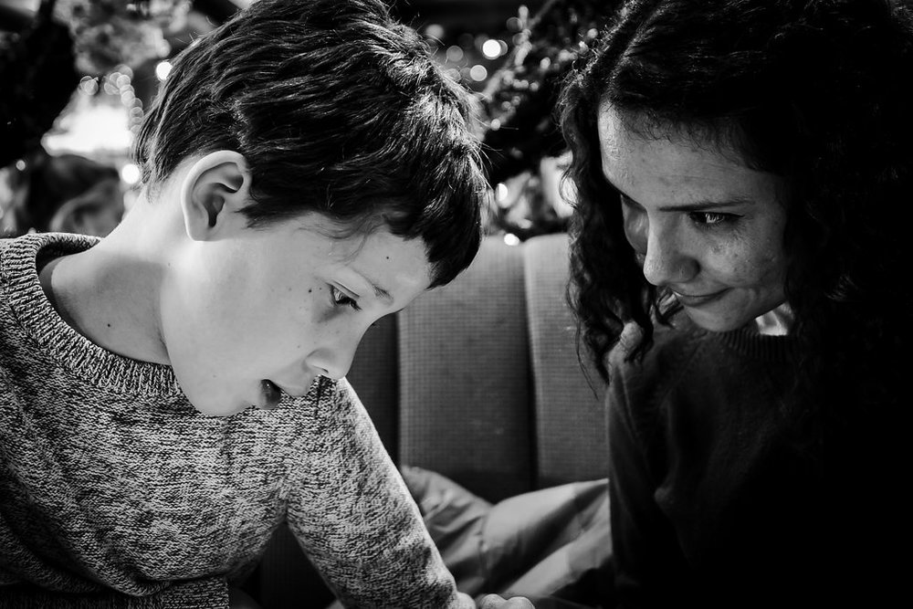 Black and white photo of a mother looking lovingly at her son at a restaurant in Denver, CO