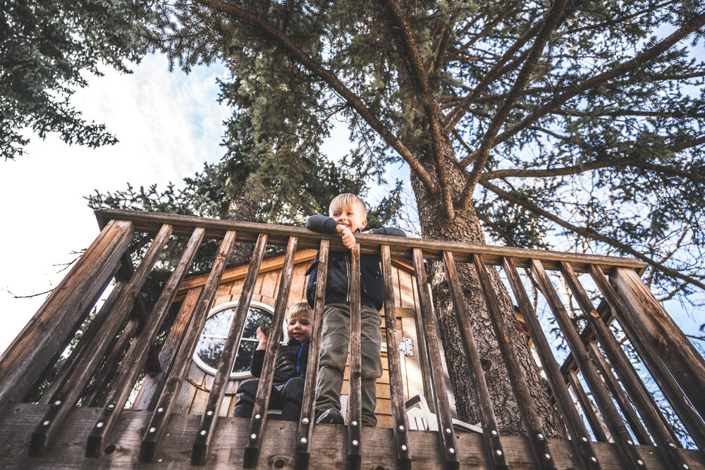 Color photo taken from below of two brothers standing on the balcony of a tree house in Park Hill, Colorado