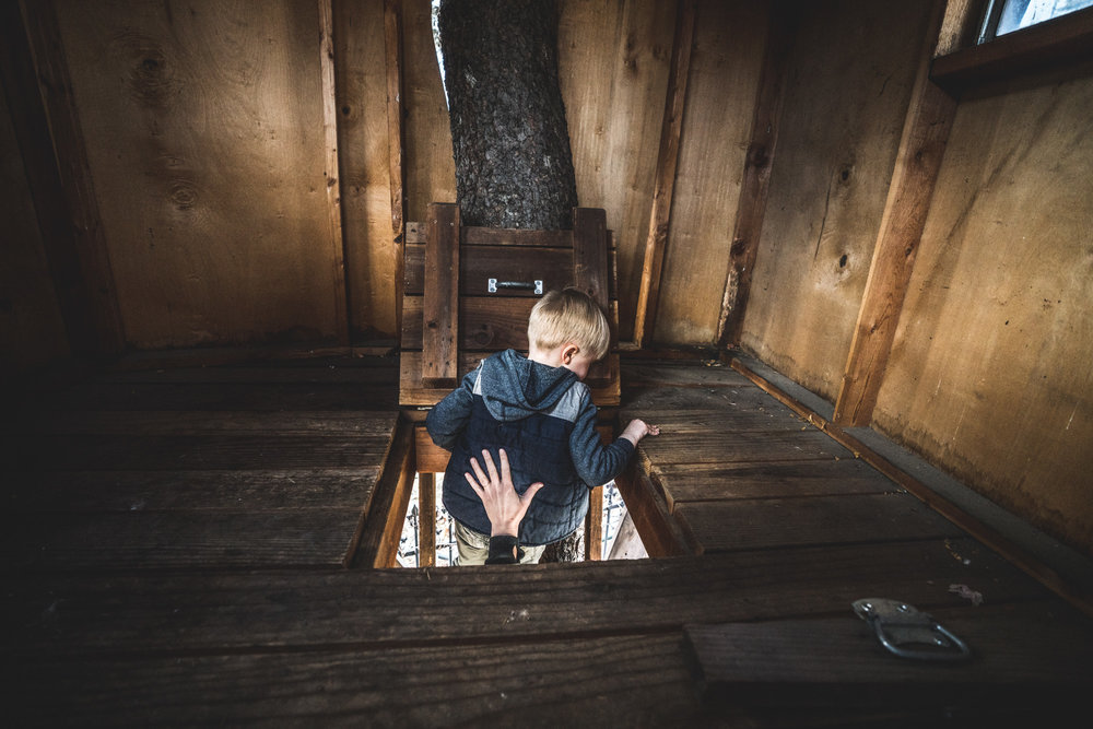 Color photo of a little boy attempting to climb out of the hatch to the tree house, his mother reaching up a hand to ensure his safe descent. Photo taken during the family's family photography session in Park Hill, Colorado