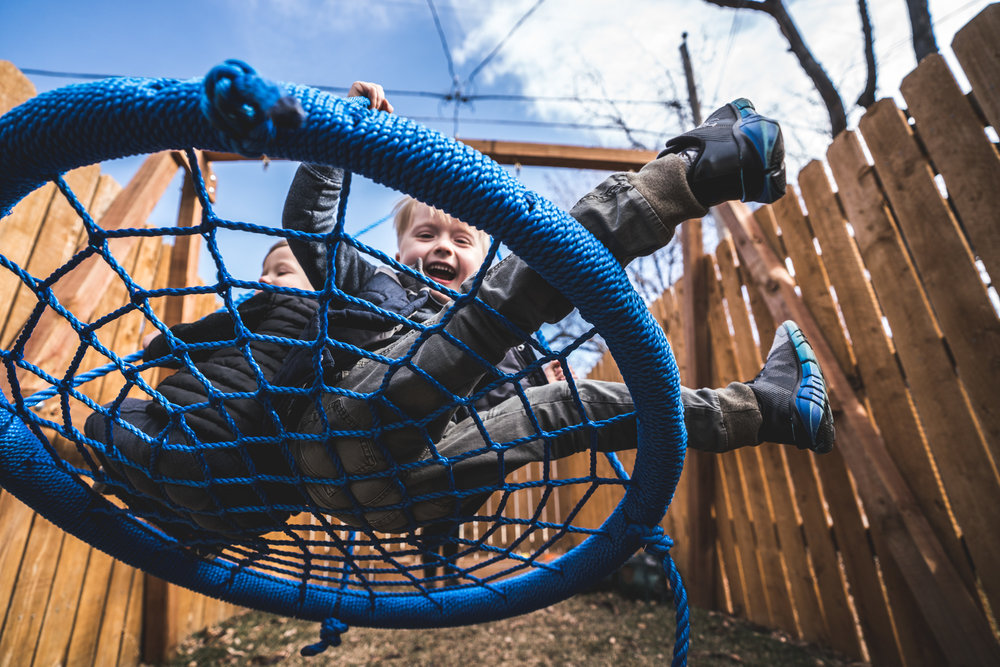 Color photo of two boys swinging high on a homemade, blue mesh swing during their photography session in Park Hill, Colorado