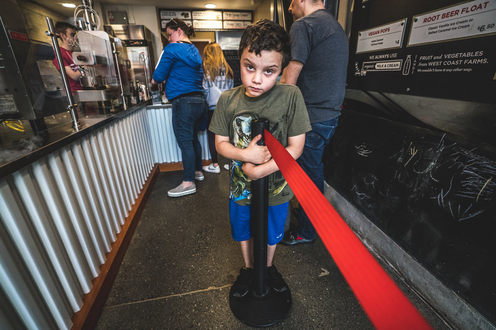 Color photo of a little boy in an ice cream shop, staring straight to camera and standing on a pylon (like he's not supposed to be)