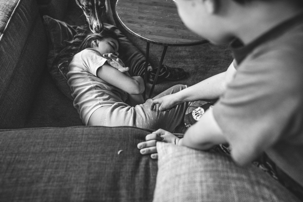 Black and white photo of a young girl lying next to the couch as her younger brother and dog try to wake her up; taken during her family's full day photography session
