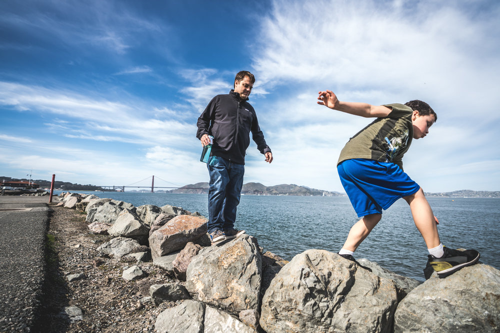 Color photo of a son and his father walking across large boulders that border the bay in San Francisco, the Golden Gate Bridge in the background. Taken during their travel day in the life photography session in Oakland and San Francisco, California.