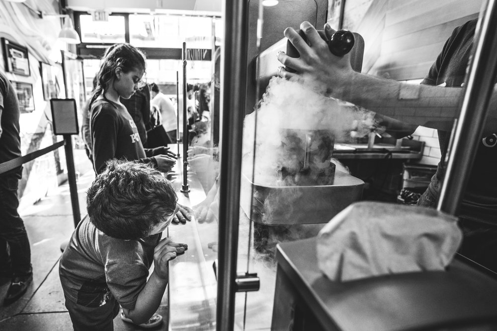 Black and white photo of a young boy watching them make nitrogen ice cream at the Smitten Ice Cream Shop in San Francisco, California