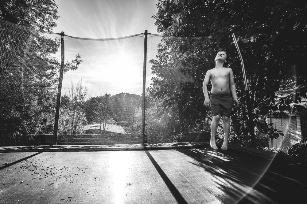 Wide black and white shot of a little boy jumping on his trampoline in his backyard in Oakland, CA