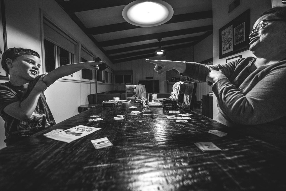 Black and white photo of a mother and son smiling as they point at each other across the table while playing a card game together, taken at their home in Oakland, California