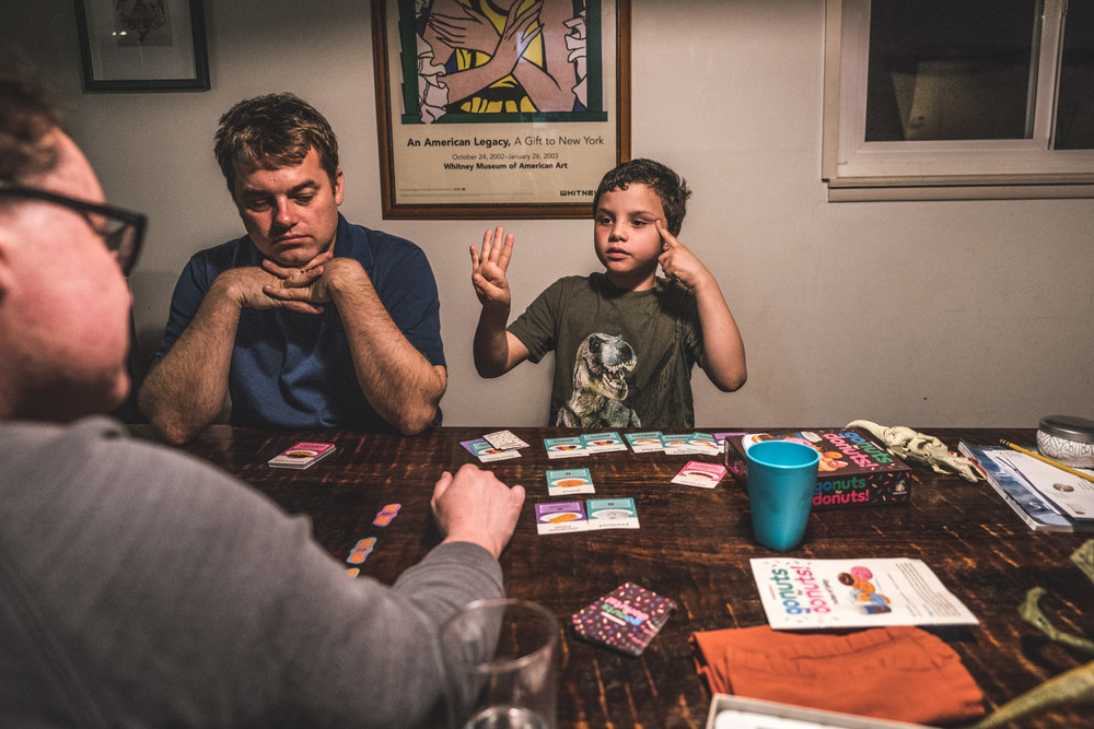 A little boy thinks hard to do the math and add up his points while he plays a card game with his parents at the kitchen table; color photograph taken at the family's home in Oakland, California during their full day in the life documentary photography session.