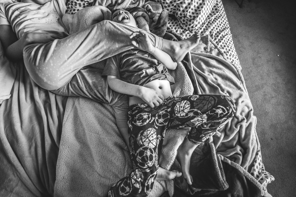 Black and white photo of a sister smooshing her brother with her leg while lying in bed while her brother laughs hysterically, Oakland, CA