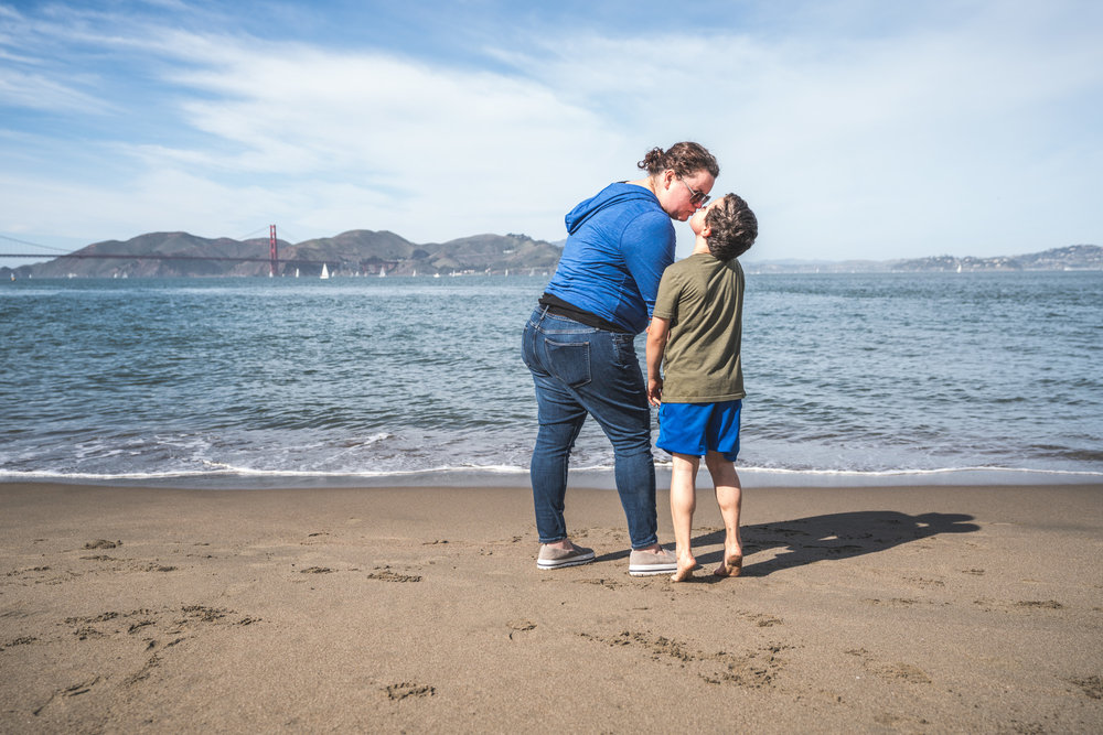 Color photo of a mother giving her son a kiss as he stands on his tippy toes to reach her; taken during their documentary photography session on the beach in San Francisco