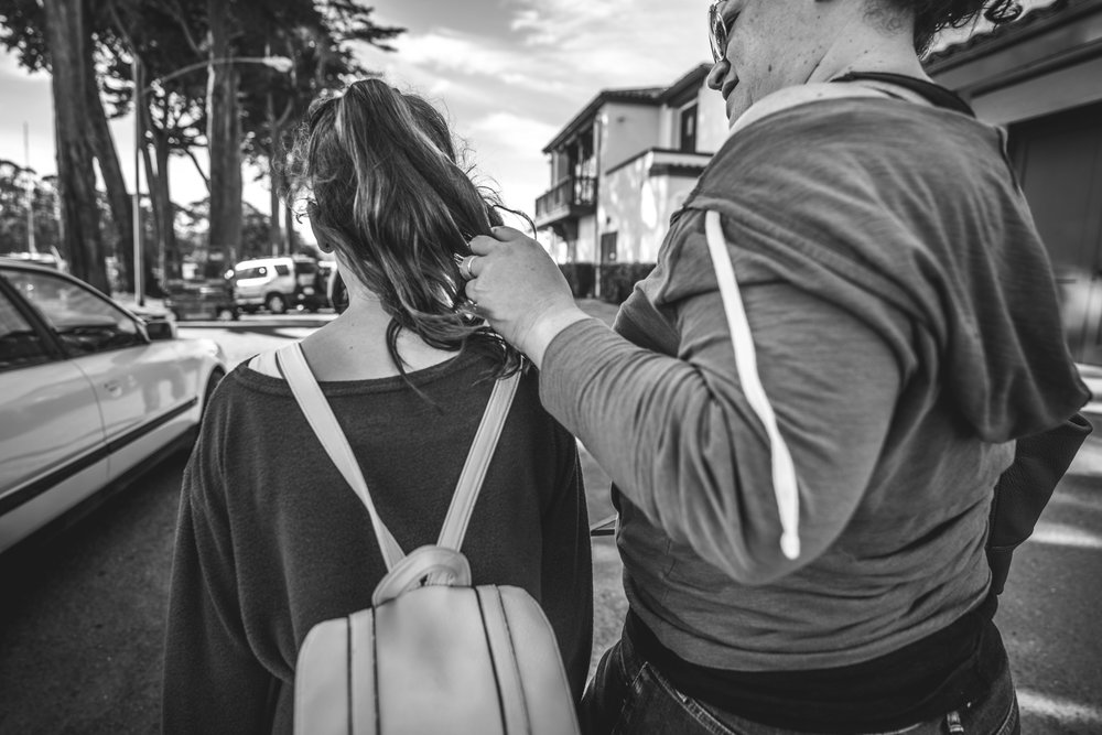 Black and white photo of a mother lovingly running her fingers through her daughter's hair as they walk down the street together in San Francisco, CA