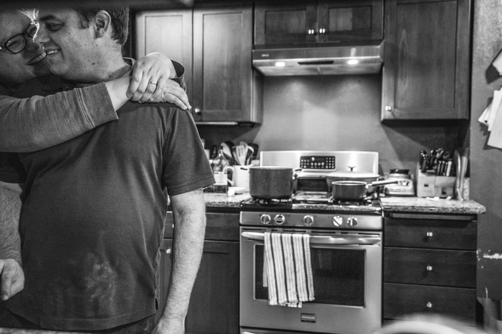 Black and white photo of a husband and wife in their kitchen, facing the camera with the husband in front and the wife behind him with her hands thrown around his neck, both smiling at each other. Taken at their home in Oakland, California during their documentary photography session