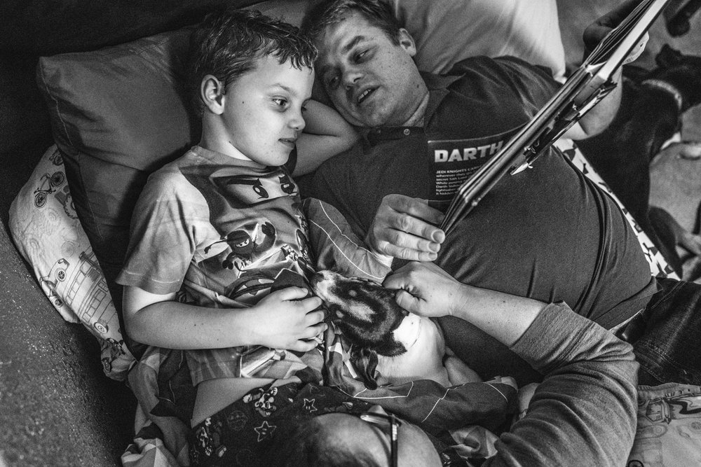 Black and white photo of a father and son reading a star war's book during story time while the mother and their little dog lie at their feet, taken during their family photography session in their home in Oakland, CA