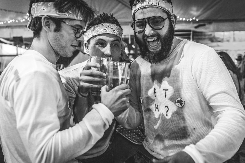 Black and white photo of three male friends wearing matching shirts and headbands toasting each other during the Autism Society of Colorado's Shamrock Stumble fundraiser in downtown Littleton, CO.