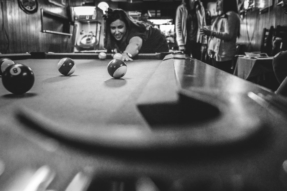 Black and white photo of a woman taking a pool shot from the perspective of the hole. Taken in the Olde Towne Tavern in Littleton, Colorado during the Autism Society of Colorado's Shamrock Stumble pub crawl fundraiser