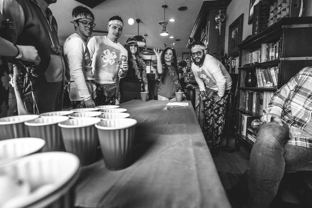 Black and white photo of a woman throwing a ball at solo cups during a game of Beer Pong as a bunch of people stand around and watch. Taken during the documentary photography event session of the Autism Society of Colorado's Shamrock Stumble fundraiser at Jake's Brew Bar.