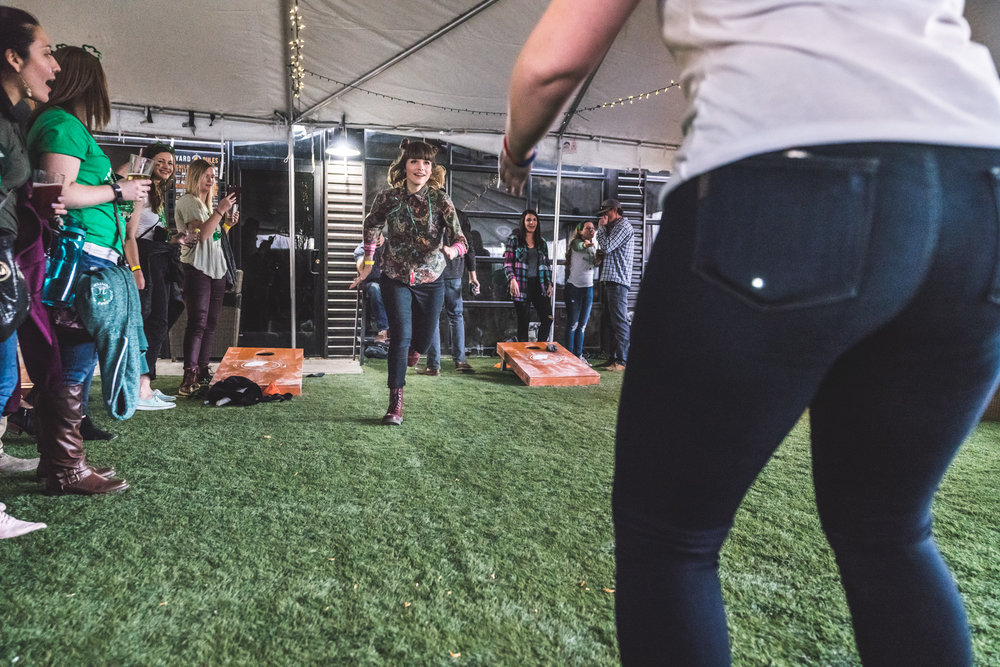 Color photo of a woman running toward another woman in a tent outside of the ViewHouse Littleton during the ASC Shamrock Stumble photography session