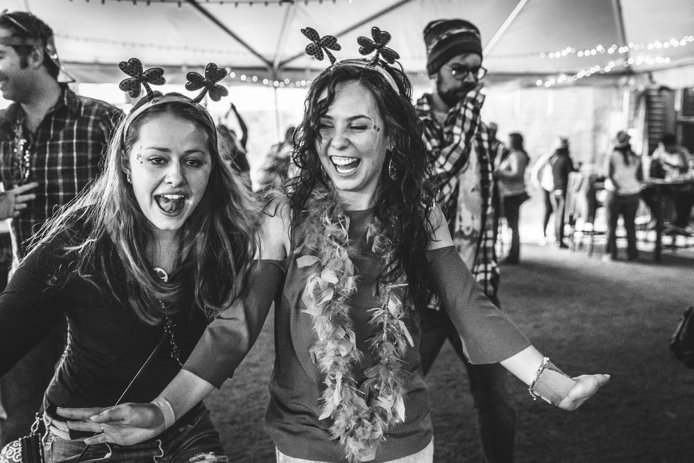 Black and white photo of two women wearing shamrock headbands and laughing and smiling during a charity event for the Autism Society of Colorado in Littleton, Colorado.