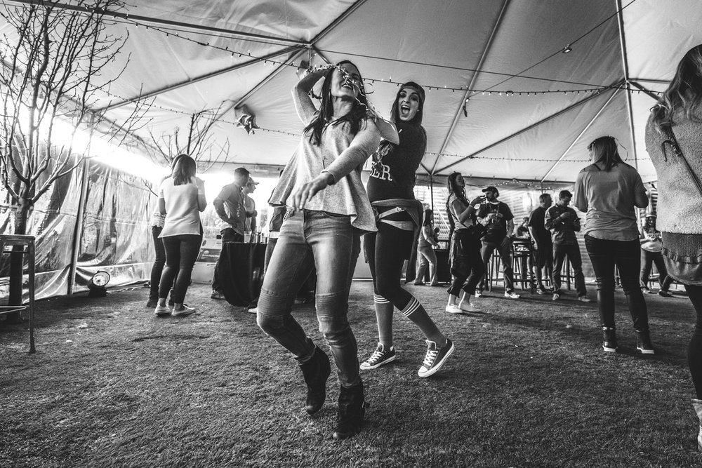 Black and white photo of two women dancing in a giant white tent during a charity event for the Autism Society of Colorado in Denve.