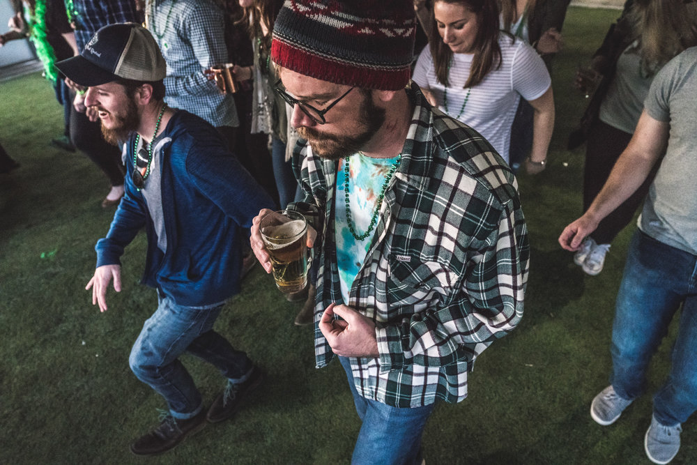 Color photo of a group of people doing a line dance and drinking beer at the Autism Society Fundraiser at the ViewHouse in Littleton, Colorado