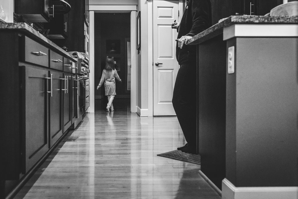 Black and white photo of a little girl sauntering out of her kitchen in Stapleton, Colorado during her in-home documentary photography session