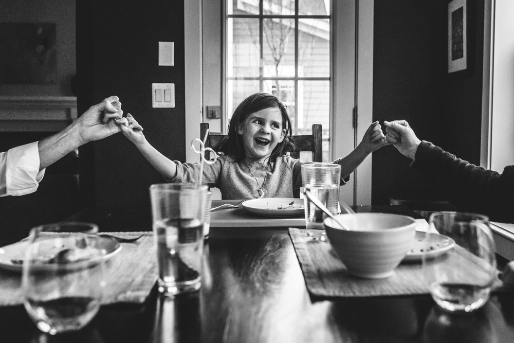 Black and white photo of a young girl sitting at the head of the kitchen table, holding her daddy's pinky with her right hand and her mommy's pinky with her left. Photo taken in their home in Stapleton, Colorado during their day-in-the-life photography session.