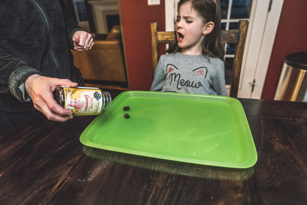 "Color photo of a mother pouring vitamins out onto a green tray for her little girl who is sitting at the table wearing a cat-ear headband and a ""meow"" shirt. Taken at their home in Denver, Colorado during their at-home photography session."