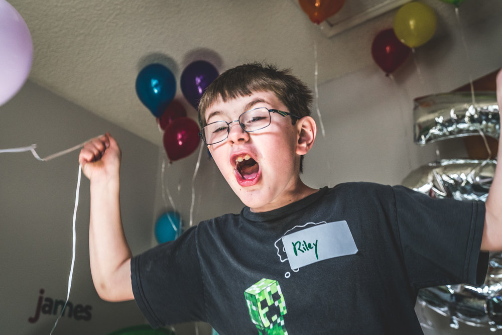 Color photo of a little boy freaking out excited over the massive quantity of balloons in the room, photo taken during his friend's birthday party in Aurora, Colorado.