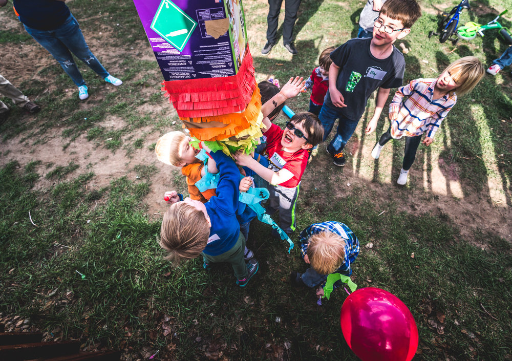 Bright colored overhead photo of a bunch of kids ripping apart a brightly colored piñata in a back yard in Aurora, Colorado