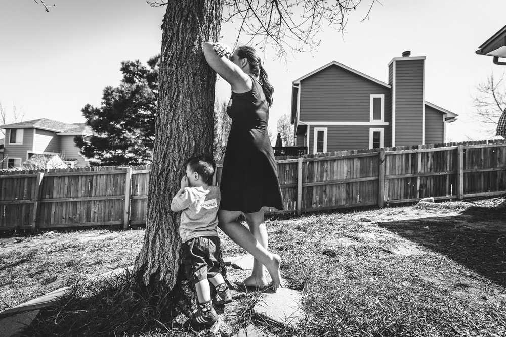 Black and white photo of a mother and son resting their heads on a tree and covering their eyes, counting to ten while playing hide and seek in their back yard in Aurora, Colorado
