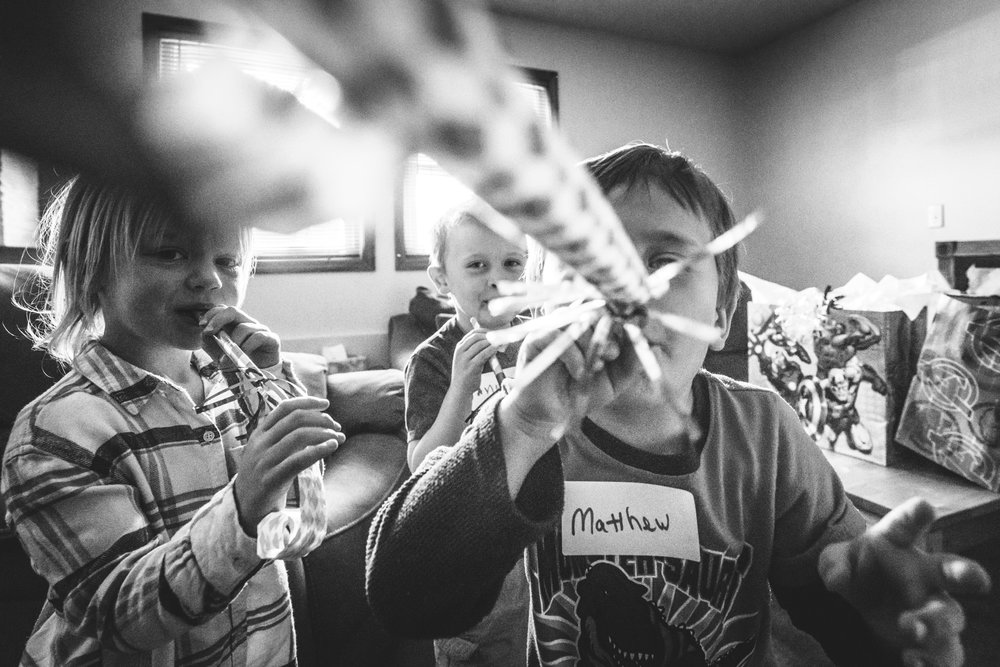 Black and white photo of a little boy blowing a party blower directly at camera while his two friends watch