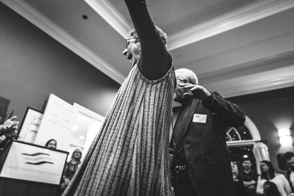 Black and white photo looking up at a woman as she raises her arms with joy and smiles wide. Taken at a non-profit wine event in Denver, Colorado.