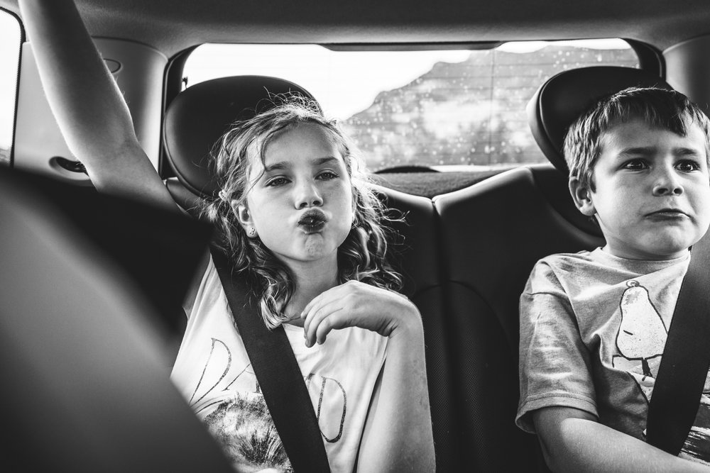 Black and white photo of two children in the back seat of a car, the young boy making a funny face and the young girl pursing her lips as she sucks on a piece of candy. Taken during their mini photo session in Estes Park, Colorado.