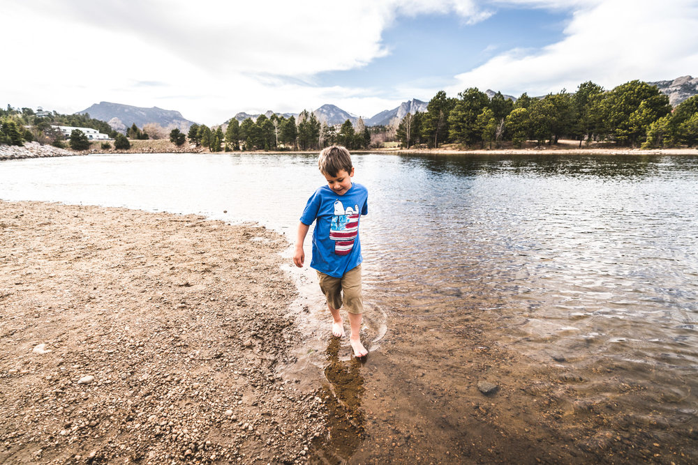 Color photo of a little boy kicking around the water in a lake in Estes Park, Colorado.