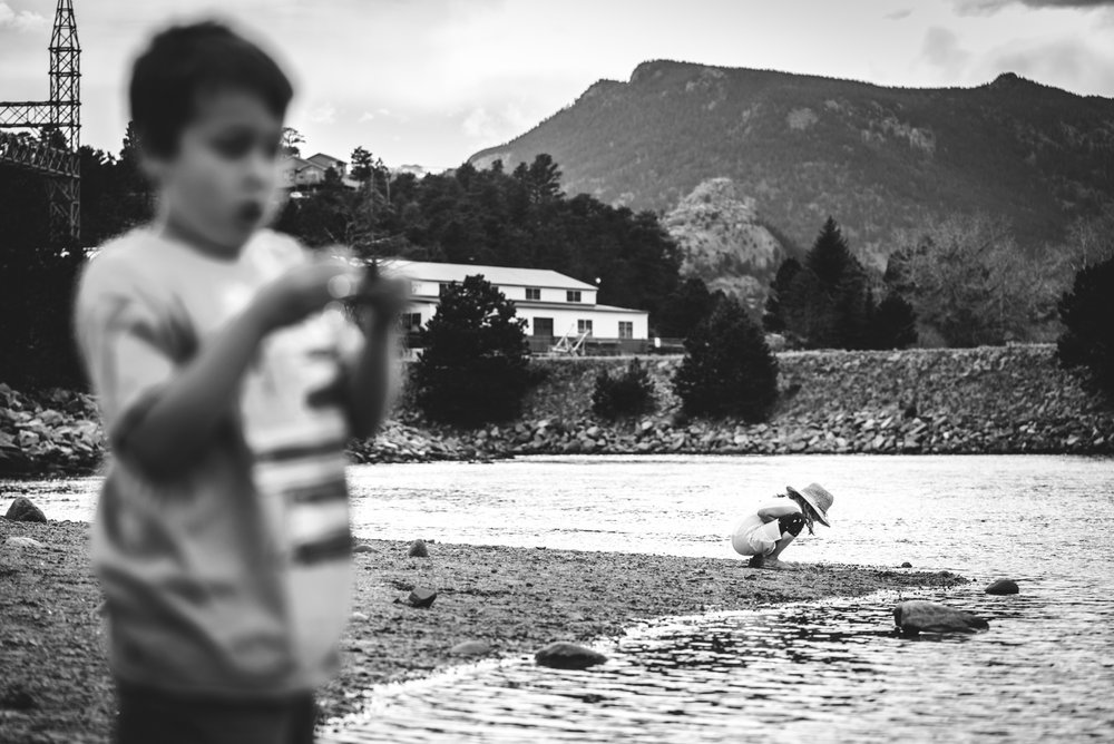 Black and white photo of a little girl bent down, inspecting something in the rocky, sandy beach of a lake in Estes Park, Colorado as her brother in the foreground looks at something in his hand.