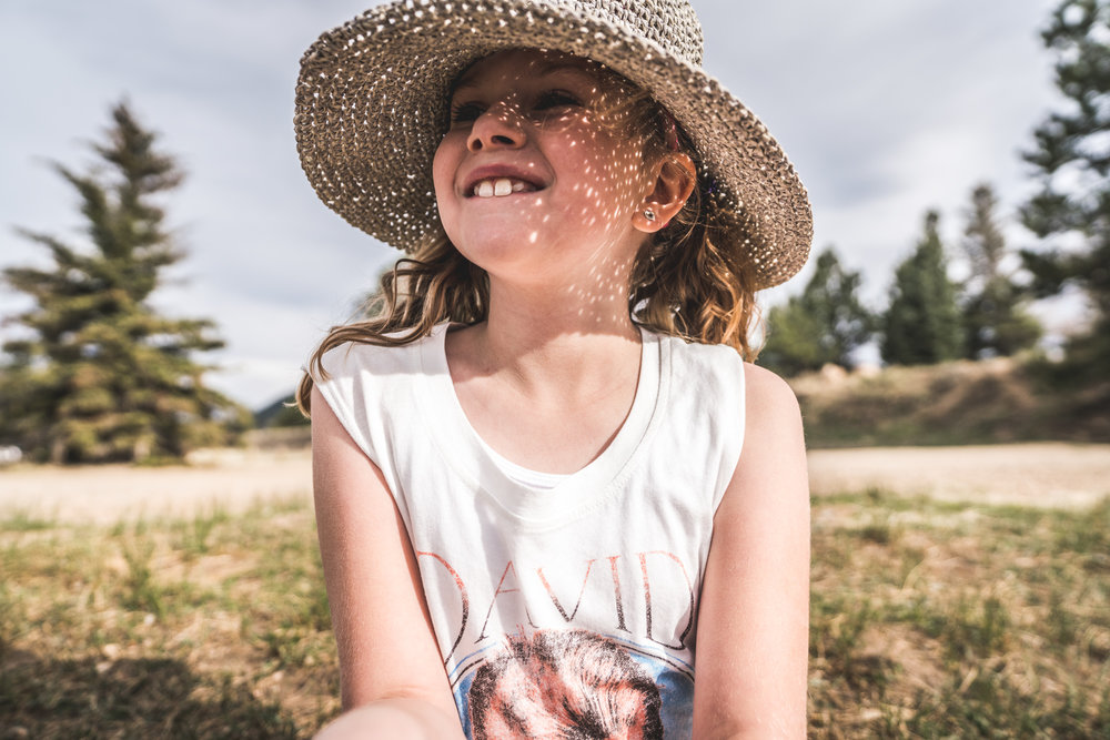 Color environmental portrait of a blond, curly-haired little girl smiling as she wears a straw hat that creates dapples of light on her face as the sun shines through it. Taken during her family documentary photo session in Estes Park, Colorado.