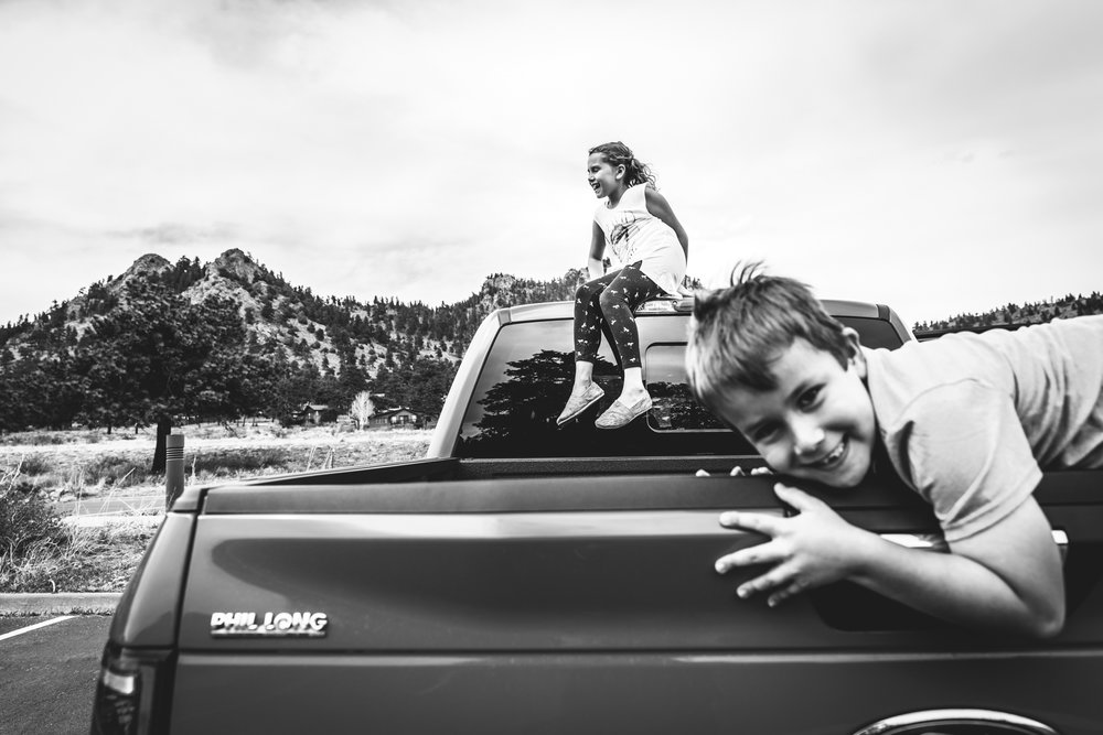 Black and white photo of two children on the back of a truck - the young boy on the tail gate, smiling at the camera, and the young girl on top of the cap, smiling and looking to her right. Taken in Estes Park, Colorado at the Rocky Mountain National Park visitor's center.