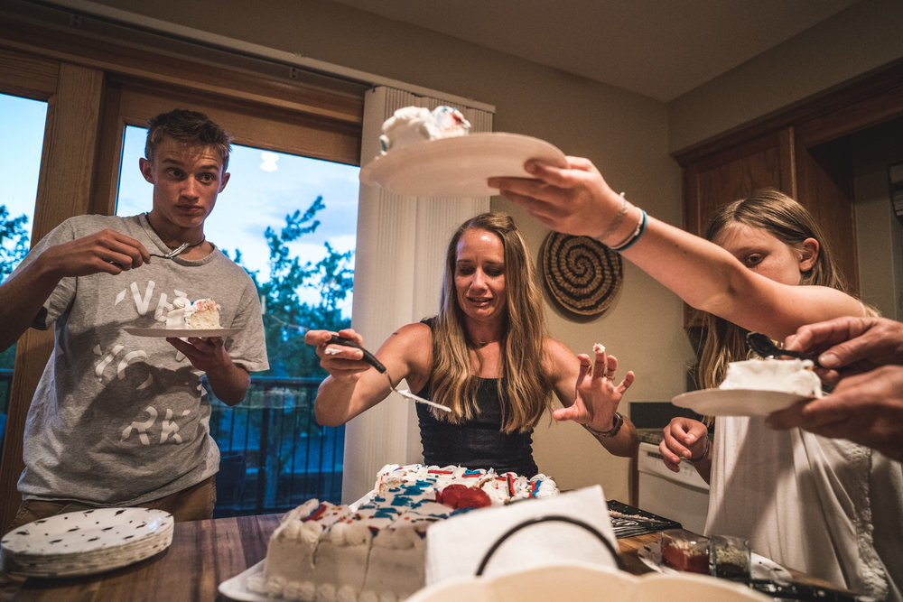 Color photo of a family in their kitchen eating graduation cake. Taken during their documentary event photography session in Denver, Colorado.