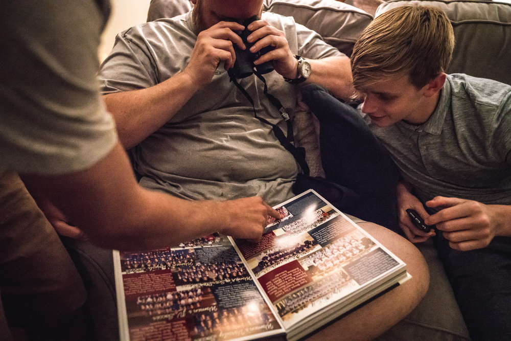 Color photo of a man looking at the yearbook on his lap through binoculars while the son to the left sitting next to him looks on and the arm of the son to his right reaches over to point out something in the book. Taken during their documentary event photography session at their home in Denver, CO.