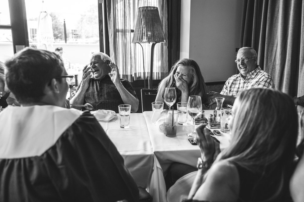 Black and white photo of a family laughing hysterically together while sitting at a table in a restaurant in Denver, CO.