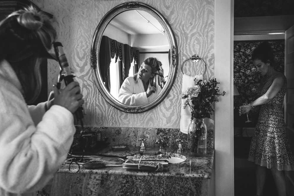 Black and white photo of a woman looking in the mirror as she curls her hair in preparation of being maid of honor in her sister's wedding while her mother checks her watch. Taken in a suite in the Hotel Boulderado in Boulder, CO.