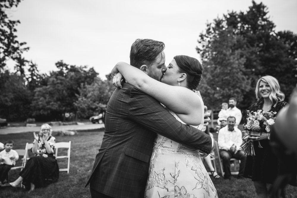 Black and white photograph of a bride and groom kissing at the end of their wedding ceremony in Chautauqua Park in Boulder, CO.