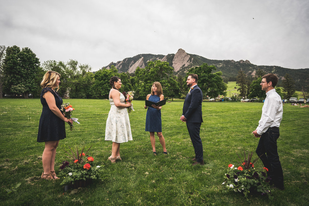 Color photo of a wedding ceremony taking place in Chautauqua Park with a woman officiant wearing a blue drive, a bride and groom, and one bridesmaid and one groomsmen.