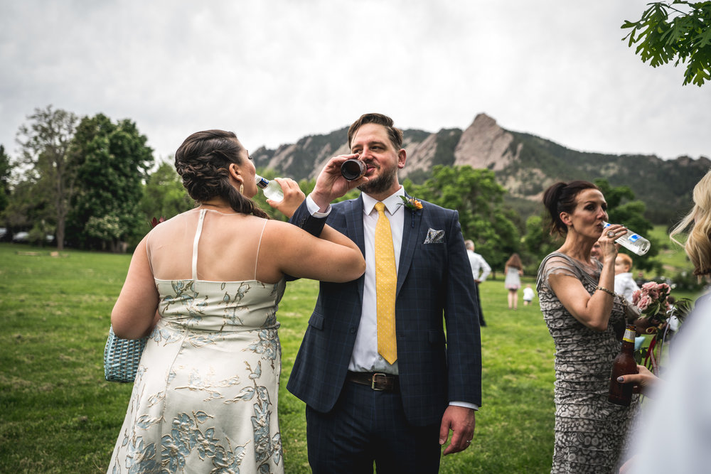 Color photo of a bride and groom linking arms and each taking a drink of their respective beers following their wedding ceremony in Chautauqua Park in Boulder, CO.