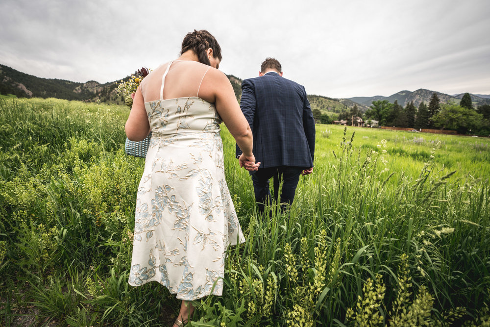 Color photograph of a bride and groom walking hand in hand in the field below the Flatirons in Boulder, Colorado.