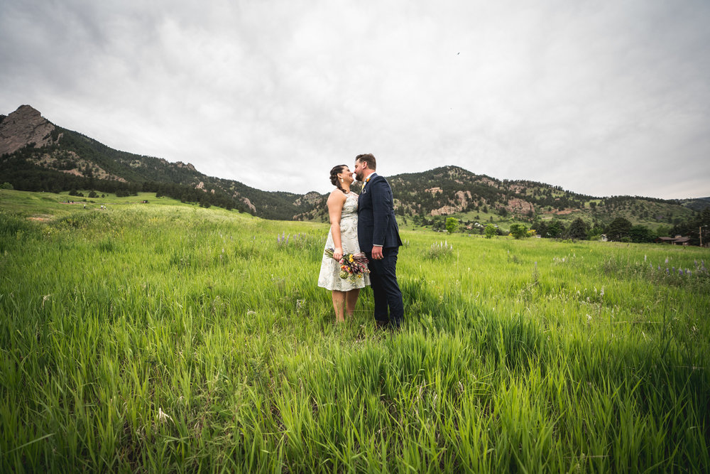 Color photograph of a bride and groom moving in to kiss each other in a field in front of the Flatiron mountains in Boulder, Colorado.