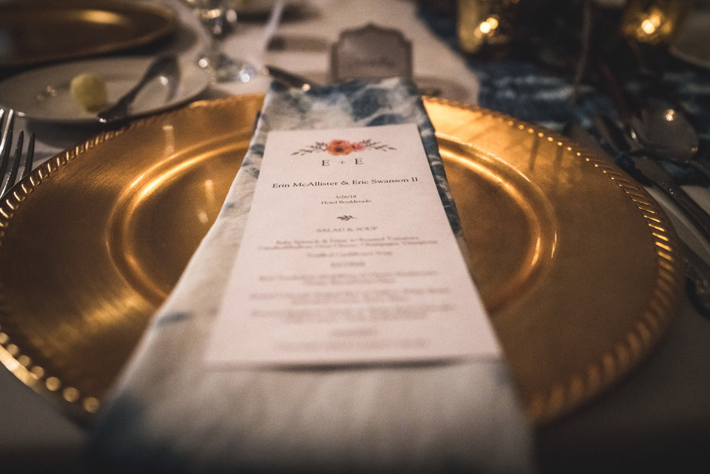 Color photo of a beautiful place setting with a gold plate and blue ombre cloth napkins in the Hotel Boulderado.