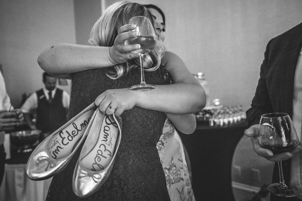 Black and white image of a bride hugging her sister and maid of honor while holding a glass of wine in one hand and her shoes in another.
