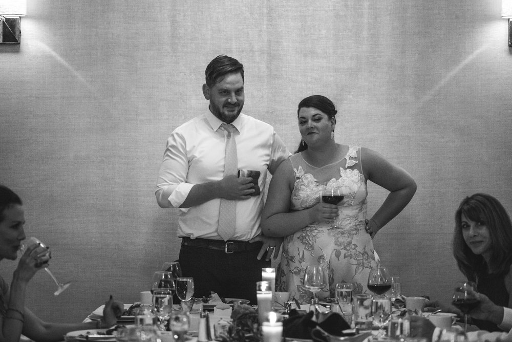 Black and white photo of the bride and groom giving a toast and looking at a guest with a funny look on their faces.