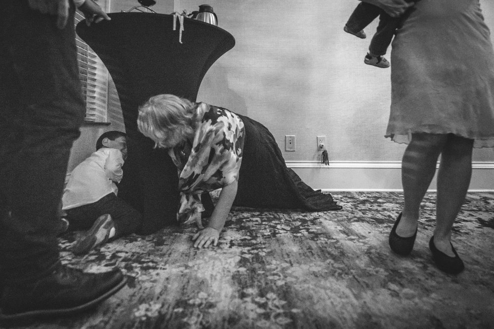 Black and white photo of a little boy playing hide and seek with his grandma, both in formal wear, during a wedding reception at the Hotel Boulderado in Boulder, CO.